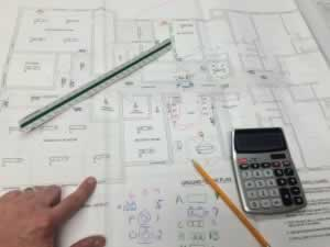 plans, hands, pencil and calculator